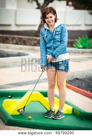 cute young woman playing golf