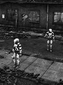 stock photo of robot  - Black and white image of two futuristic robots holding guns fighting a war in a ruined city - JPG