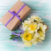 image of gift wrapped  - Bunch of fresh spring yellow daffodils flowers amd wrapped gift box on turquoise painted wooden planks - JPG