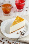picture of cheesecake  - One slice of banana cheesecake on a white plate with two glasses of drinks - JPG