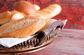 stock photo of bread rolls  - Basket of golden crusty fresh bread rolls in assorted shapes on a rustic wooden table ready to accompany dinner close up side angle view - JPG