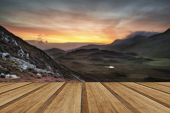 foto of cloud formation  - Stunning sunrise mountain landscape with vibrant colors and beautiful cloud formations with wooden planks floor - JPG
