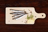 stock photo of peppercorns  - Delicious fresh sardines on wooden kitchen board with lemon rosemary and colorful peppercorns on wooden background - JPG