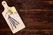 picture of peppercorns  - Delicious fresh sardines on wooden kitchen board with lemon rosemary and colorful peppercorns on wooden background with copy space - JPG
