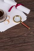 stock photo of private investigator  - Coffee cup paper sheets and detective magnifying glass on old Wooden table - JPG