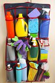 picture of household  - Household chemicals in holder hanging on wooden door - JPG