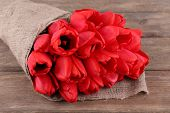image of sackcloth  - Bouquet of red tulips wrapped in sackcloth on wooden background - JPG