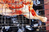 pic of charcoal  - grilling spiced chicken in grid on charcoal bbq with tomatoes and vegetables - JPG