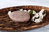 foto of acupressure  - Acupuncture needles on wooden plate with pebble and flowering branch - JPG