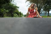 stock photo of hippy  - Young hippie girl sitting on the road with lush summer greenery behind her - JPG