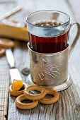 stock photo of bagel  - Glass of tea in an old cup holder and small bagels - JPG