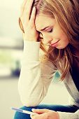 picture of pregnancy test  - Sad young woman holding pregnancy test - JPG