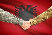 stock photo of albania  - Soldiers shaking hands with flag on background  - JPG