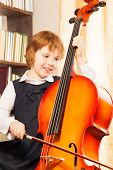 picture of cello  - Happy girl in school uniform playing on the cello near the piano indoors - JPG