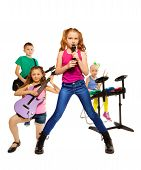 stock photo of singing  - Four children playing on musical instruments together as rock group and girl singing as vocalist in front on white background - JPG