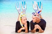 pic of flipper  - Happy diver couple lying down on the beach - JPG