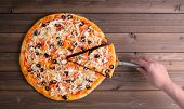 picture of hot fresh pizza  - Pizza with cheese and pizza paddle on wooden table background - JPG