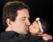 stock photo of daddy  - A Daddy holding and kissing his newborn daughter - JPG