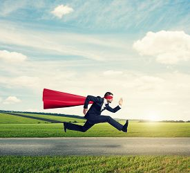 image of running-late  - serious businessman wearing like superhero very fast running on the road over green fields and blue sky - JPG
