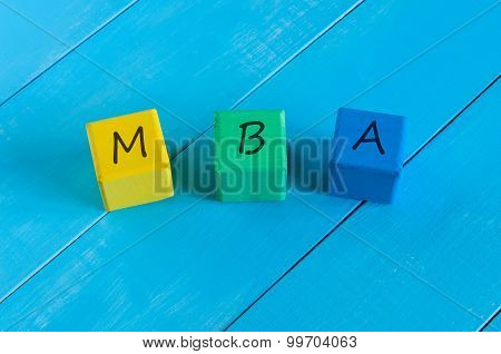 MBA or Master of Business Administration sign on wood children's colourful cubes, blocks and blue wo