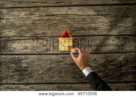 Overhead View Of Real Estate Or Insurance Agent Constucting A House From A Wooden Cubes