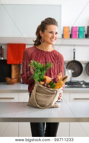 An Elegant Woman Is Showing Off Her Bag Of Fresh Autumn Veggies