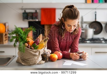 Woman In Kitchen Reading Shopping List With Shopping And Receipt