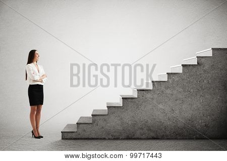 successful businesswoman in formal wear looking up at concrete stairs over grey background