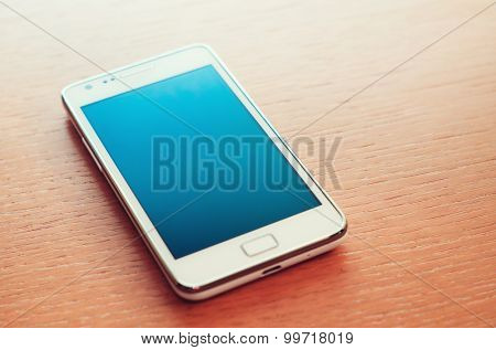 Turned off smartphone on wooden background