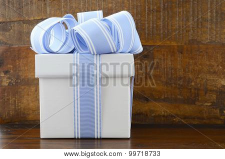 Blue And White Gift On Dark Wood Background.