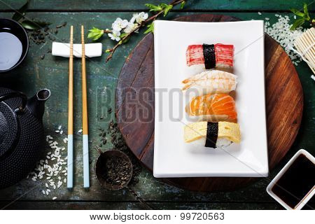 Asian food background (black iron tea set and sushi on rustic table)