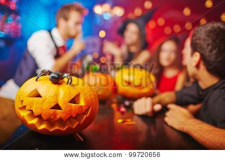Jack-o-lantern on bar counter and friends on background