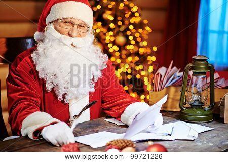 Santa Claus looking at camera while reading Christmas letter