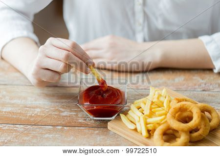 fast food, people and unhealthy eating concept - close up of hands with deep-fried squid rings, dipping french fries into ketchup bowl on wooden table