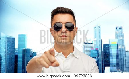 summer, accessories, style, gesture and people concept - face of middle aged latin man in white polo t-shirt and sunglasses pointing finger on you over city background