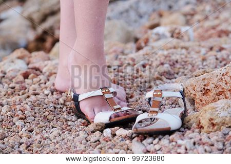 Feet of the girl putting on sandals