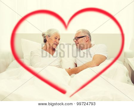 family, bedtime, valentines day, love and people concept - happy senior coupler lying in bad and talking at home with big red heart shape