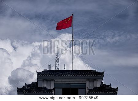 Chinese Flag Flying Over A Building