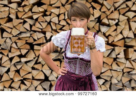 Young Woman In A Dirndl Drinking A Cold Beer