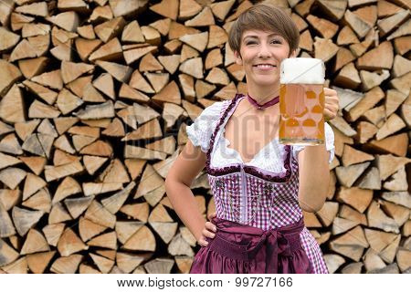 Happy Young Bavarian Woman Toasting With A Beer