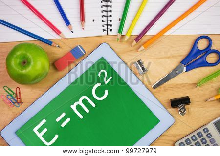 Theory of relativity against students table with school supplies