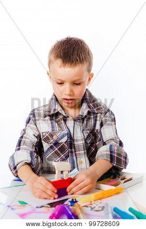 Preschooler boy playing with plasticine