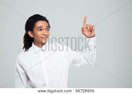 Portrait of afro american businessman pointing finger up over gray background