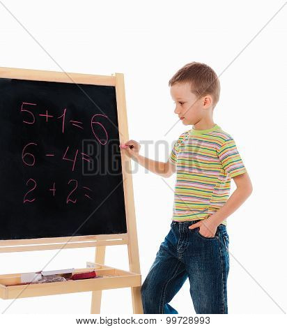 chalkboard with math examples and a boy standing nearby
