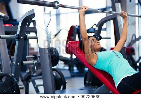 Beautiful woman doing exercises with barbell on the bench in fitness gym