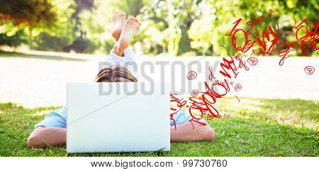 letter and number jumble against pretty woman using laptop in park