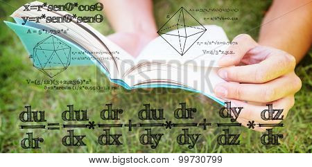 Math equation against pretty woman reading book in park