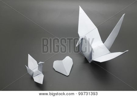 White origami crane and heart between, bird paper