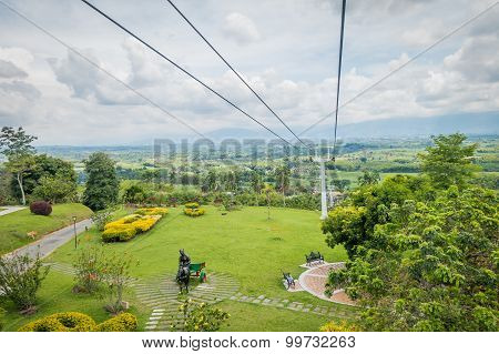 Downward view of cable car path inside National Coffe Park, shot from passenger perspective