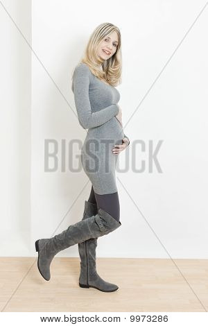 Standing Pregnant Woman Wearing Fashionable Gray Boots